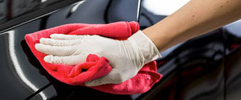 Gloved hand cleaning tar off of a car surface with a towel